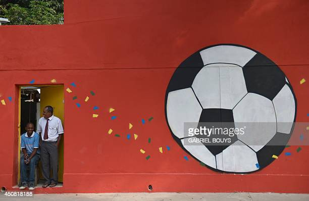 Two men look out of a door in a wall decorated with a football mural on June 18 2014 outside the Maracana Stadium in Rio de Janeiro during the 2014...