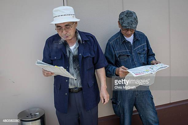 Two men look over the form guide ahead of the days racing during Keirin races at Kawasaki Velodrome on July 11 2015 in Kawasaki Japan Keirin is a...
