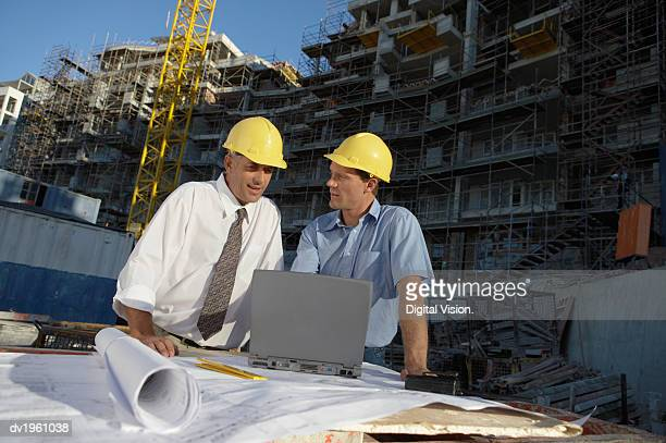 Two Men Looking at a Laptop Computer on a Building Site