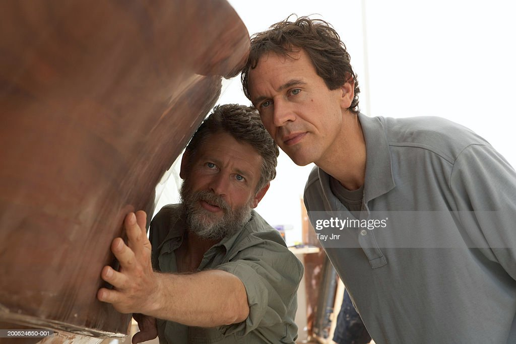 Two men looking at boat in workshop : Stock Photo