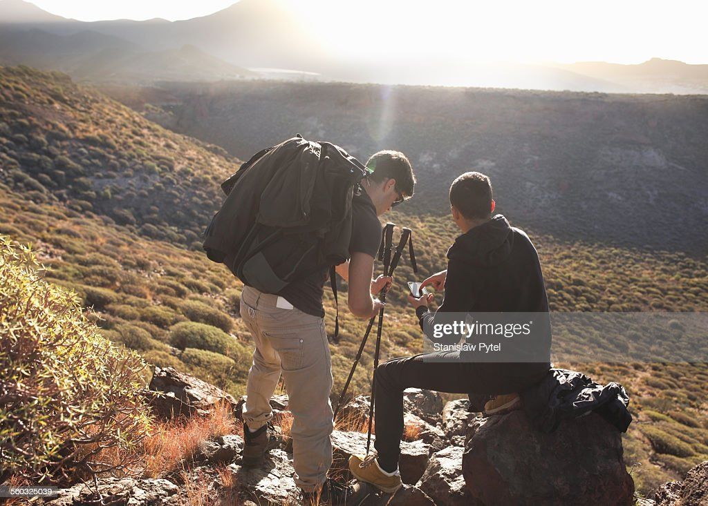 Two men looking at gps, trekking in mountains : Stock Photo