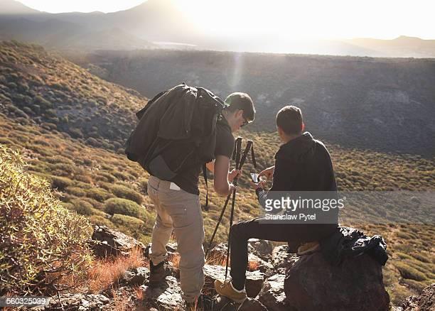 Two men looking at gps, trekking in mountains
