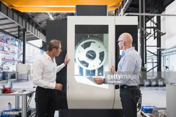Two men looking at machine on factory shop floor