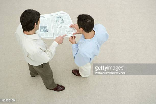 Two men looking at newspaper together, overhead view