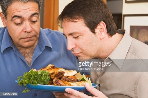 Two men looking at plate of food