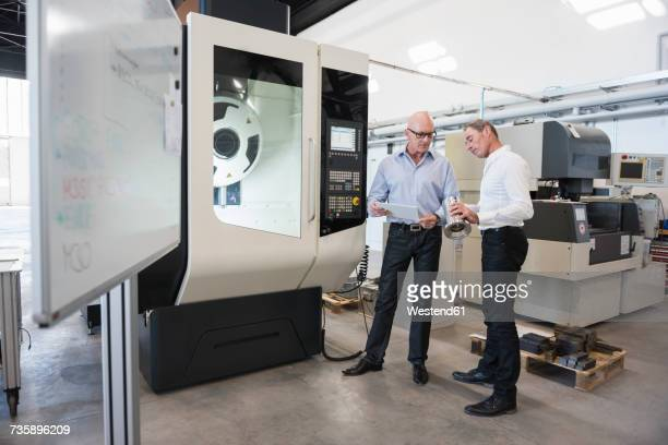 Two men looking at tablet and product in factory