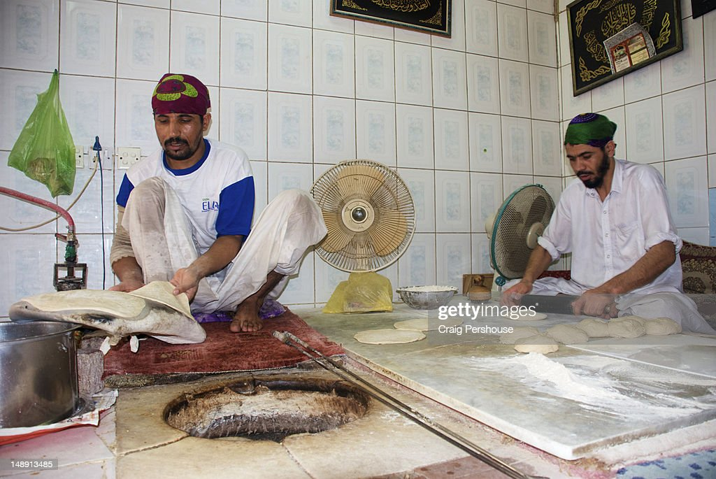 Two men making Middle Eastern-style flat bread in bakery. : Stock Photo