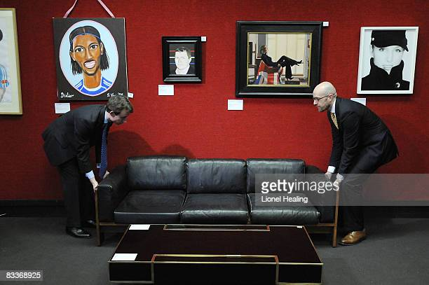 Two men move a sofa under portraits of sports stars on October 21 2008 in London Bonhams will auction several portraits of sports stars including...