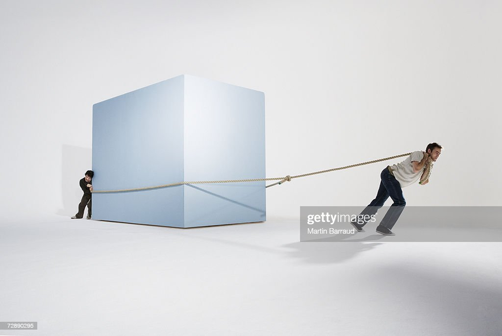 Two men moving giant box with rope