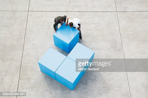 Two men moving large blue block, elevated view