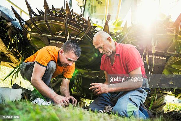 Two men near a combine harvester changing parts