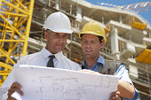 Two Men on a Building Site Looking at Blueprints
