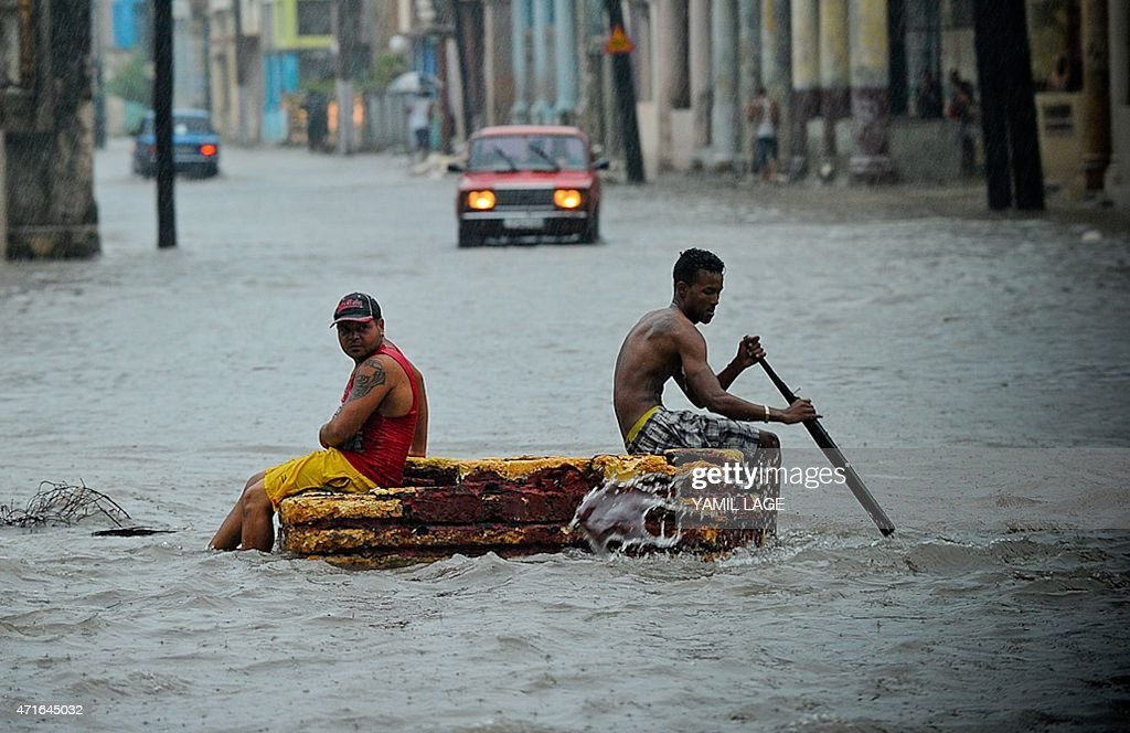 Two men on a makeshift raft wade through a flooded street during an intense rainstorm in Havana on April 29 2015 Two people were killed three...