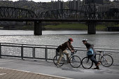 Two men on bicycles colliding on pavement by river