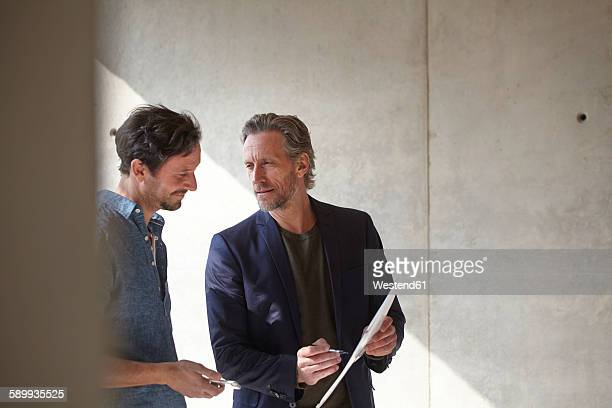 Two men on construction site discussing document