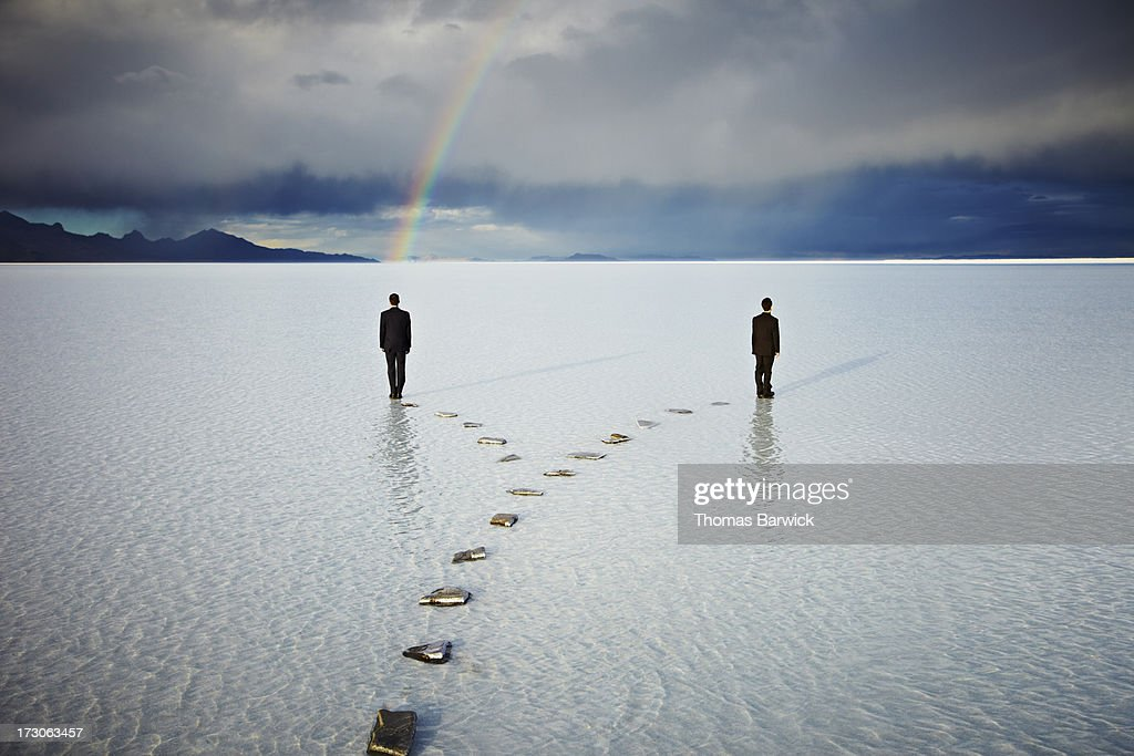 Two men on forked pathway in water under rainbow : Stock Photo