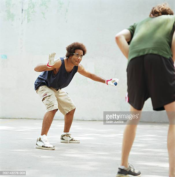 Two men on handball court, one about to serve