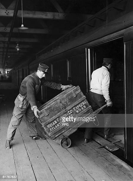 Two men one of whom is armed load Wells Fargo express packages onto a train USA circa 1925