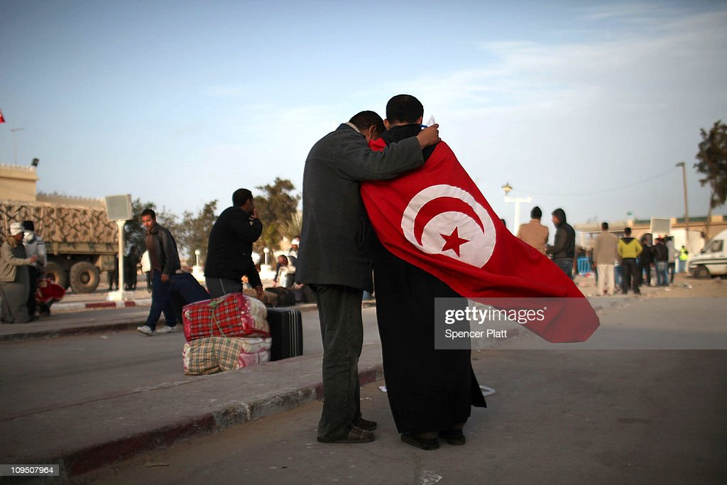 Two men one wearing the flag of Tunisia stand at the border of Libya on February 28 2011 in Ras Jdir Tunisia As fighting continues in and around the...