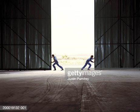 Two men opening warehouse doors