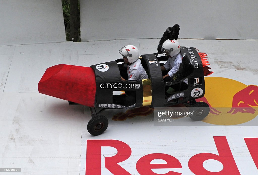 Two men operate a lipstick-shaped vehicle during a race organized by the Red Bull Soapbox Race at the Taipei University of the Arts on September 29, 2013. More then fifty vehicles take part in this 400-meter long's race. AFP PHOTO / Sam Yeh