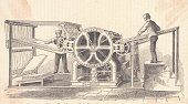 Two men operating rotary press