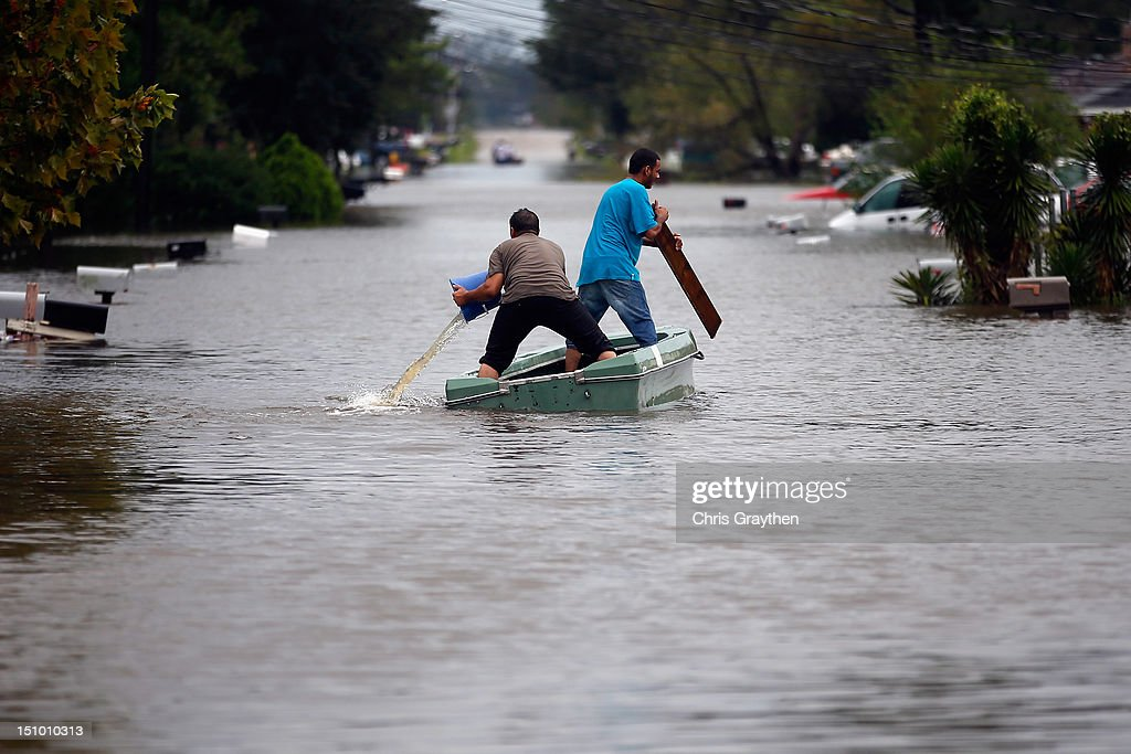 Two men paddle a boat in flood waters from Hurricane Isaac on August 30 2012 in Reserve Louisiana Isaac downgraded Wednesday to a tropical depression...