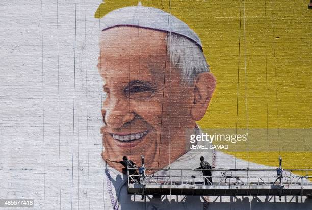 Two men paint a mural of Pope Francis on the wall of a highrise building in New York on August 28 2015 Pope Francis will visit the US on September...
