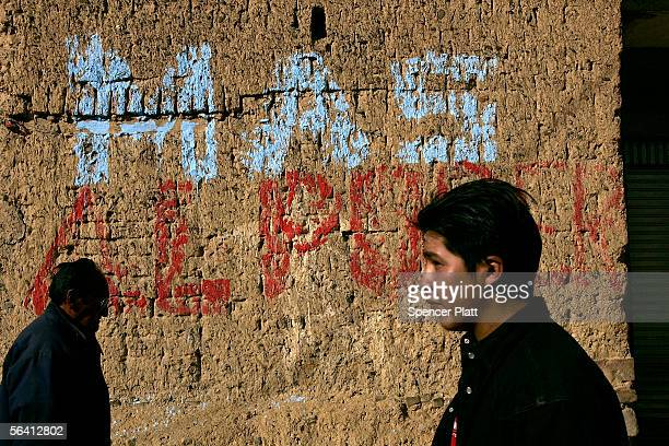Two men pass a wall spray painted with the Bolivian Presidential candidate Evo Morales`s party MAS the December 10 2005 in El Alto Bolivia Bolivia...