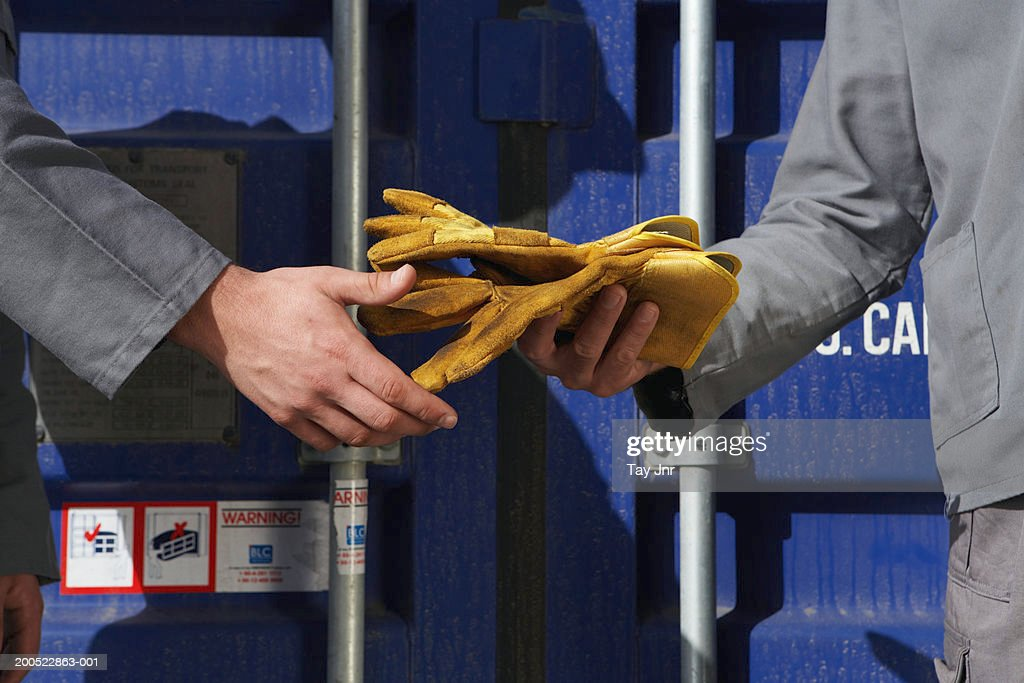 Two men passing gloves beside cargo container, mid section