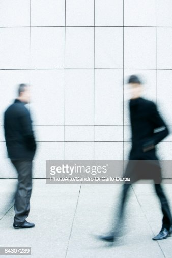 Two men passing one another as they walk along the sidewalk