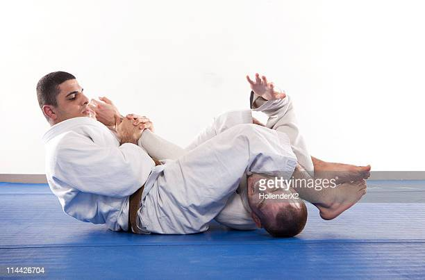 Two men performing Jiu Jitsu Martial Arts holds.