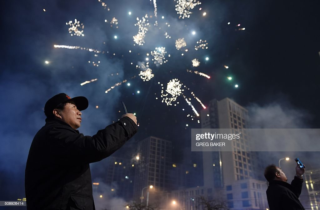 Two men photograph fireworks on a street in Beijing early on February 8, 2016 for the Lunar New Year celebrations which marks the start of the year of the monkey. / AFP / GREG BAKER