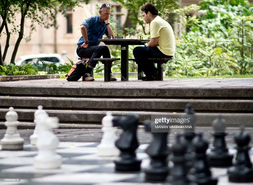 Two men play a game of chess on an outdoor board next to a giant chessboard (foreground) in Sydney's Hyde Park on January 3, 2013. Spread over 40 acres in Sydney's central business district, Hyde Park is the oldest public parkland in Australia.