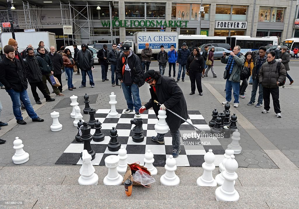 Two men play chess with large pieces on a board February 22, 2013 in New York's Union Square Park. AFP PHOTO/Stan HONDA