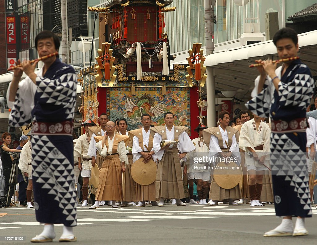 Two men play flutes as people stand front of the Yamahoko during the annual Kyoto Gion Festival on July 17, 2013 in Kyoto, Japan. The Gion festival is one of three biggest Japanese festivals. dating back to the 9th century, the festival is part of a ritual intended to satisfy the Gods that brought on fire, floods and earthquakes. During the festival the streets are decorated with lanterns and many of the women dress in 'yukata', summer kimonos.