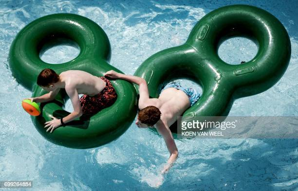 Two men play in the Duinrell amusement park on June 21 2017 in Wassenaar as Europe sizzled in a continentwide heatwave Thermometers were still...