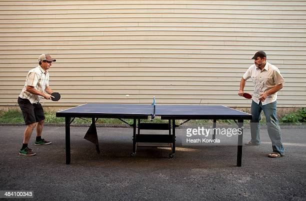 Two men play ping pong outside.