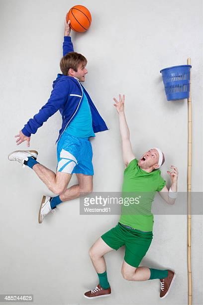 Two men playing basket ball