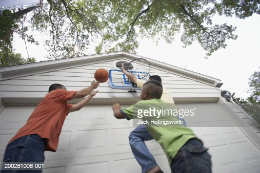 Two men playing basketball with boy, low angle view