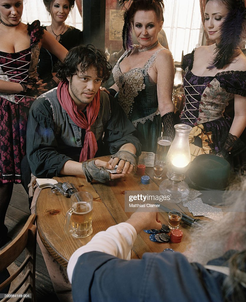 Two men playing cards with showgirls beside them at bar : Stock Photo