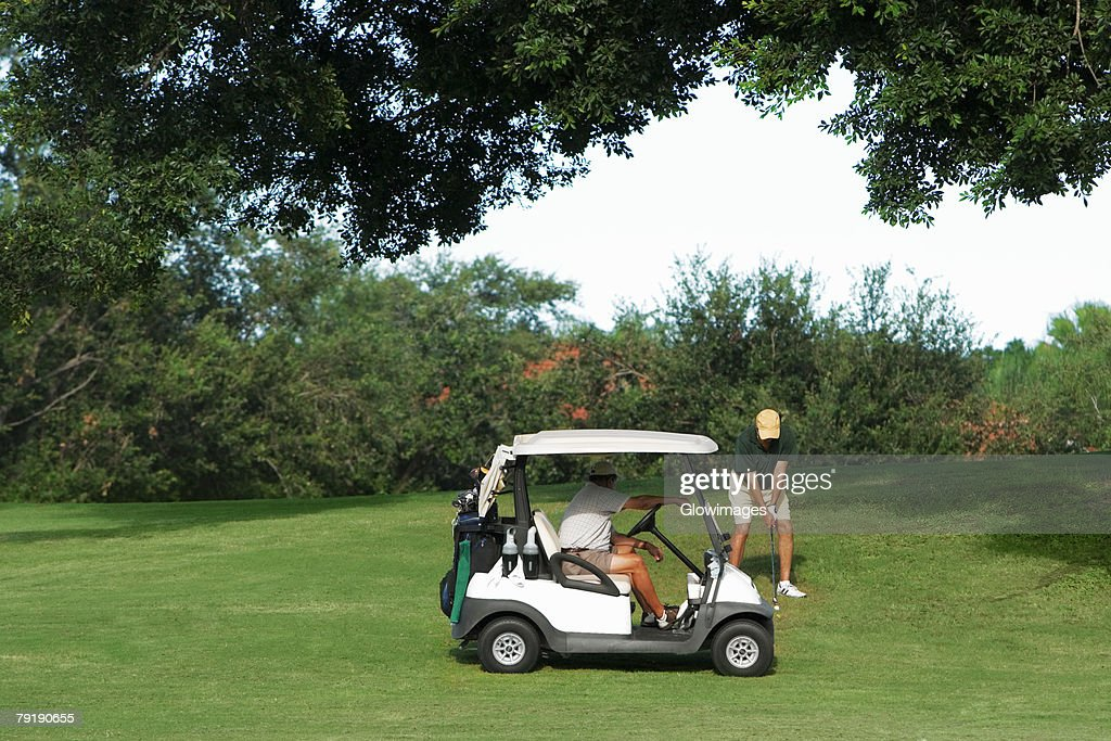 Two men playing golf in a golf course : Foto de stock
