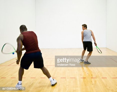 Two men playing racquetball indoors, rear view