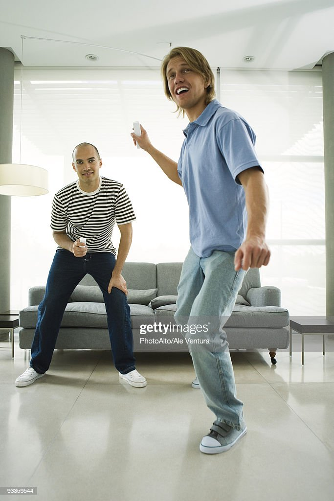 Two men playing video games with wireless controllers : Stock Photo