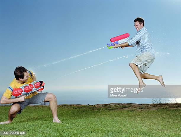 Two men playing with water guns, one man in mid-air jump