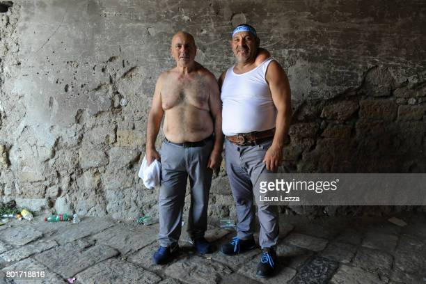Two men poses for a photo just after the annual Festa dei Gigli with his shoulder strain called 'patana' or 'pataniello' caused by having carried a...