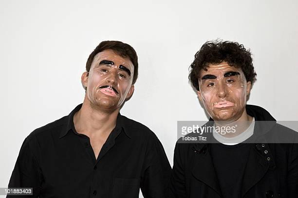 Two men posing in novelty masks,  Melbourne, Victoria, Australia