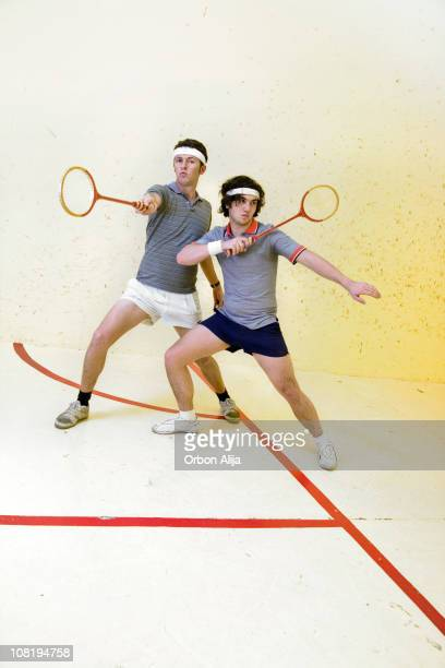 Two Men Posing on Court with Squash Rackets