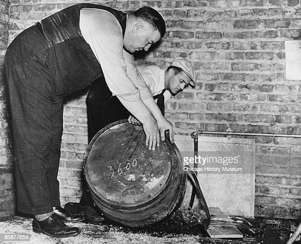 Two men pour out the contents of barrels of confiscated moonshine Chicago ca1920s Homedistilled moonshine was fermented in wooden barrels to make it...
