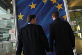 Two men prepare to walk through a glass door decorated as the flag of the European Union at the Berlaymont building of the European Commission on...